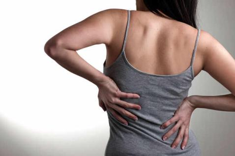 Woman holding her back due to pain