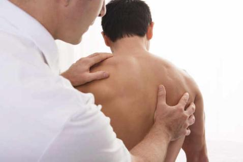 Chiropractor performing back work on a male patient
